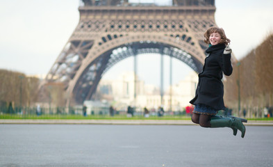 Happy young girl jumping near the Eiffel tower