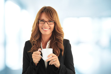Smiling businesswoman having a coffebreak