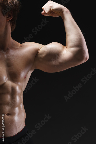 Cropped picture of muscle man posing in studio