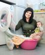 woman with baby putting clothes in to washing machine