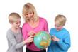 Mutter sucht mit Kindern Reiseziel auf dem Globus
