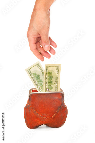 Hand putting banknotes in a purse