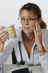 Medical practitioner sitting at desk with a drink