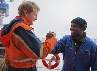 European deck officer friendly shakes a hand of African motorman