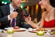 Attractive young couple drinking red wine in restaurant