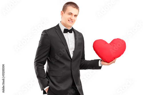 A young man wearing black suit and holding a red heart