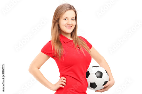 A young smiling female holding a soccer ball