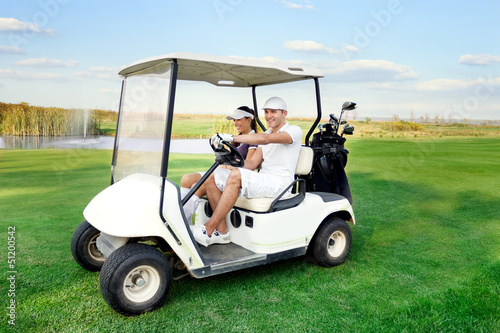 happy couple driving a golf-cart