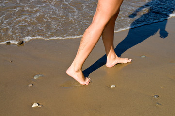 Women's feet are in the sand at the beach