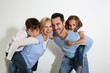 Family of four standing on white background