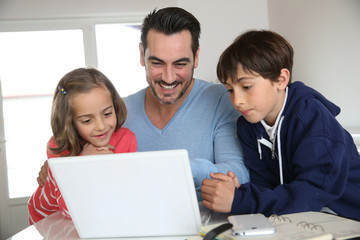 Man with children using laptop at home