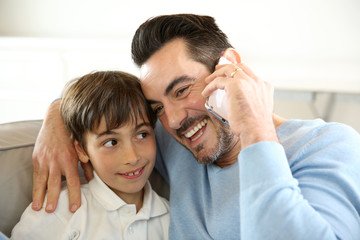 Little boy with dad playing with smartphone