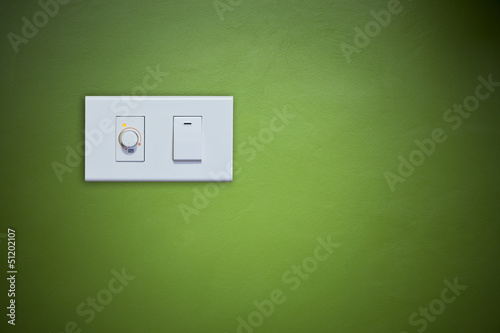 switch on electric appliance on green wall