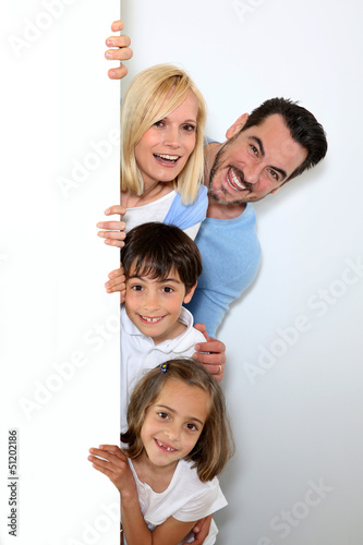 Family hiding behind message board