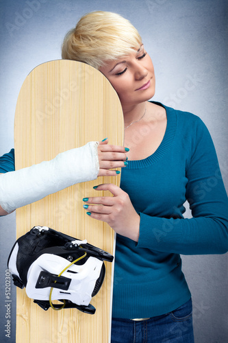 Woman with broken arm hugging her snowboard