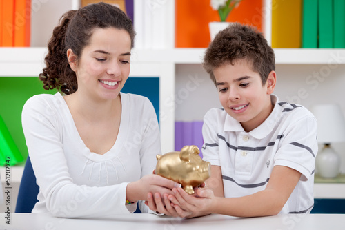 Two children holding piggybank