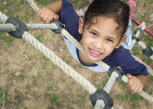 A cute girl is climbing on the rope ladder