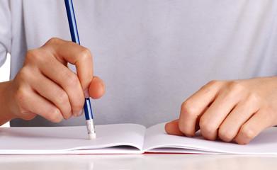 Manos borrando, escribiendo en un cuaderno.