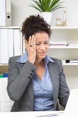 Frau mit Kopfschmerzen im Büro