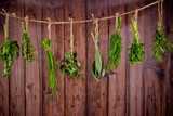 Fresh herbs hanging on wooden background