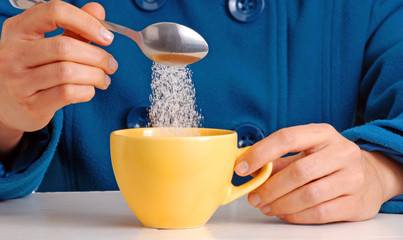 Colocando azúcar en una taza de café,cucharada de azúcar.