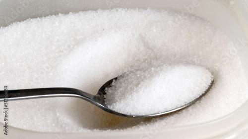 Porción de azúcar en una cuchara,cucharada de azúcar.