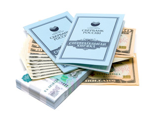 Two savings books lie on a stack of money on white background