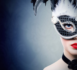 Beautiful girl in black carnival mask