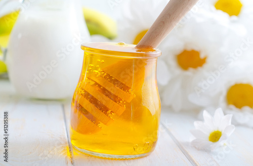 fresh honey in the glass bank and milk in jug