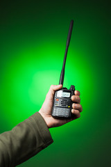 professional walkie-talkie radio in hand on green