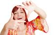 Frau hält Finger als Rahmen vor Gesicht