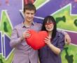 Teens with heart near graffiti wall.