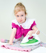 Cute little girl ironing clothes