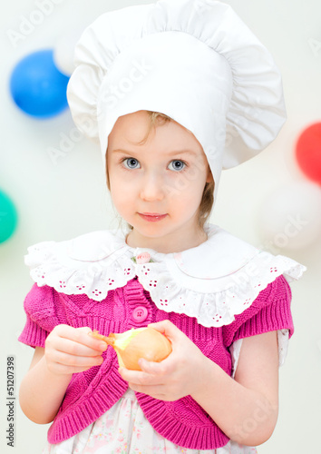 Little girl in chief hat cooking dinner