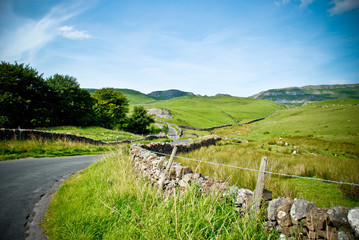 Yorkshire Dales with stone wall, green hills and blue skies