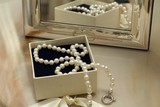 Pearl necklace in a gift box in front of a mirror