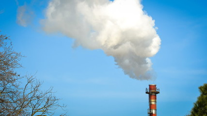 Time lapse video of industrial smoke from chimney on blue sky.