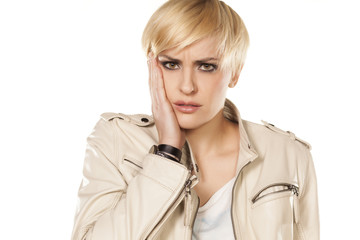 short hair blonde girl has a toothache on white background