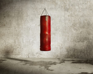 Grungy martial arts training room, red boxing bag