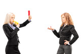 Businesswoman showing a red card to another businesswoman