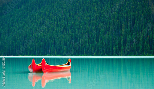 Zdjęcia na płótnie, fototapety, obrazy : Canoes floating peacufully on Lake Louise near Banff.