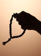 male hand with rosary, on brown background