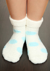 Legs female in socks with polka dots on laminate floor