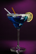 Blue cocktail in glass on color background