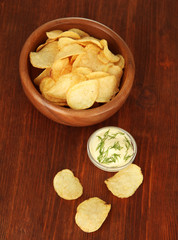 Potato chips  in wooden bowl and sauce, on wooden background