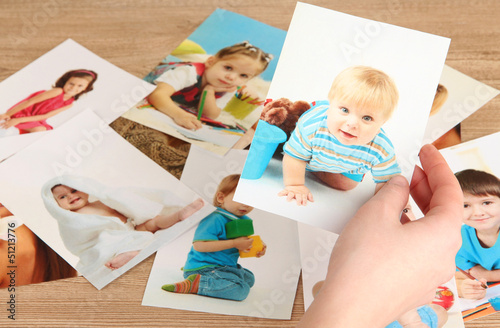 Photos in hands on wooden table