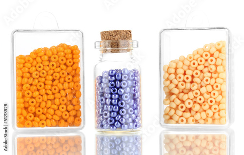 Colorful beads heap in boxes and glass bottle isolated on white