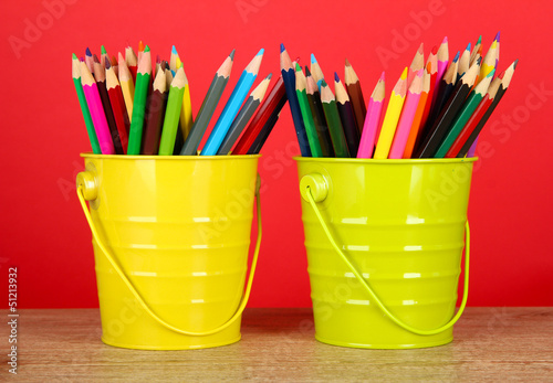 Colorful pencils in two pails on table on red background
