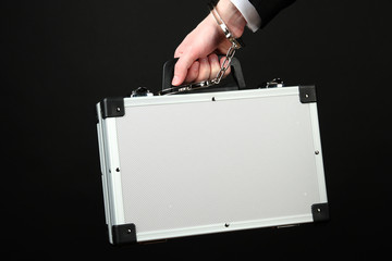 Hand with handcuff and suitcase, isolated on black