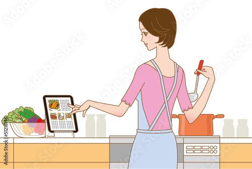 料理する女性 タブレットでレシピ確認